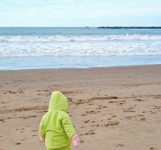 A young child walking on a beach