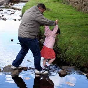 A man and a girl crossing a stream
