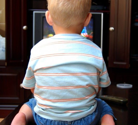 A young boy watching the TV